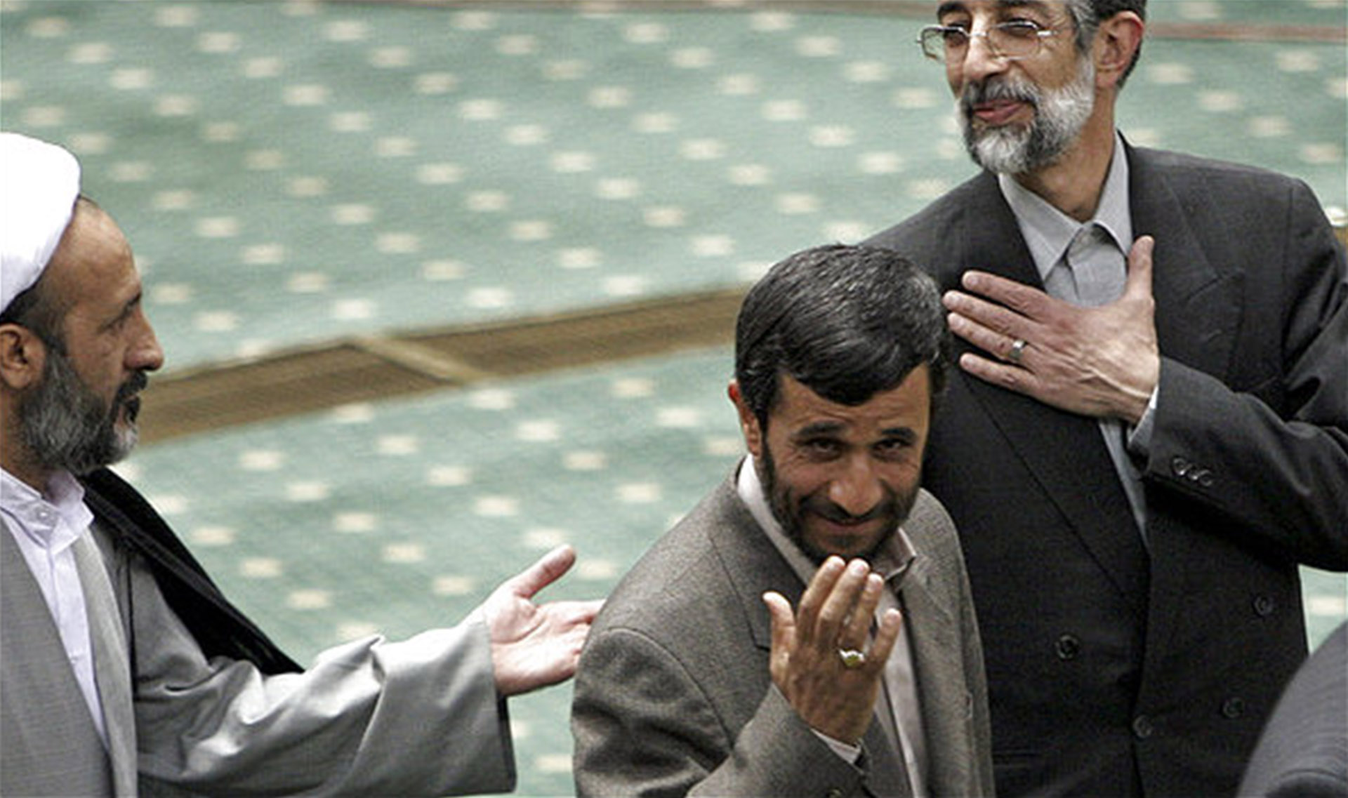 "Iranian President Mahmoud Ahmadinejad, center, gestures as he arrives in a conference for supporting the Palestinians in Tehran, Iran, Friday, April 14 2006. Ahmadinejad called Israel a ""rotten, dried tree"" that will be annihiliated by ""one storm."" (AP Photo/Vahid Salemi)"