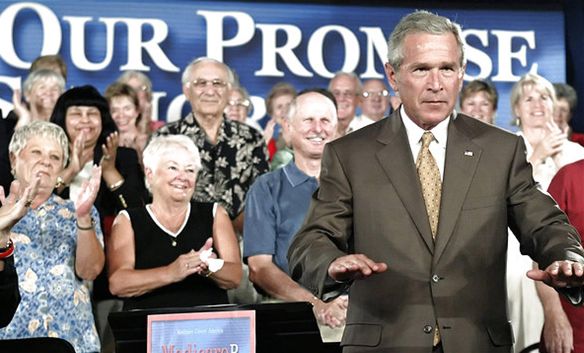U.S. President George W. Bush tries to quieten down the crowd before the start of a town hall-style meeting at a retirement community in El Mirage, Arizona, August 29, 2005. Bush talked about Medicare prescription-drug benefits with the senior citizens. REUTERS/Jeff Mitchell