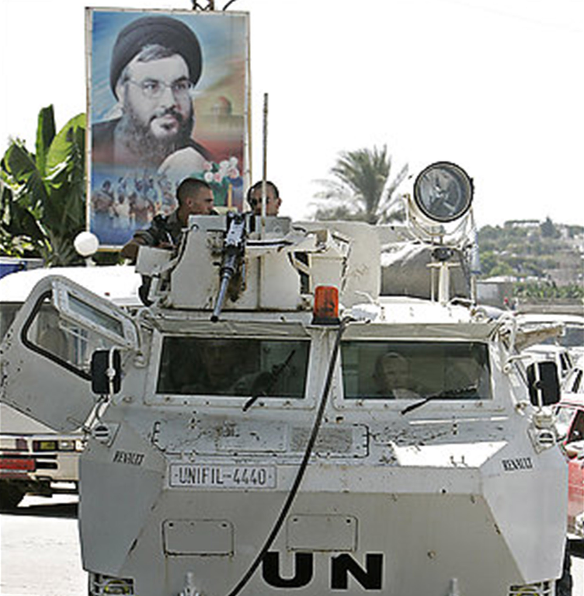 Backdropped by a poster of Hezbollah leader Sheik Hassan Nasrallah, United Nations peacekeepers from France, sit atop their armoured personnel carrier in the outskirts of the southern port city of Tyre, Lebanon, Tuesday, Aug. 15, 2006. The international community was scrambling Tuesday to put together a fortified U.N. peacekeeping force for southern Lebanon, as Israeli forces began a pullout that many fear could create a dangerous vacuum. (AP Photo/Lefteris Pitarakis)