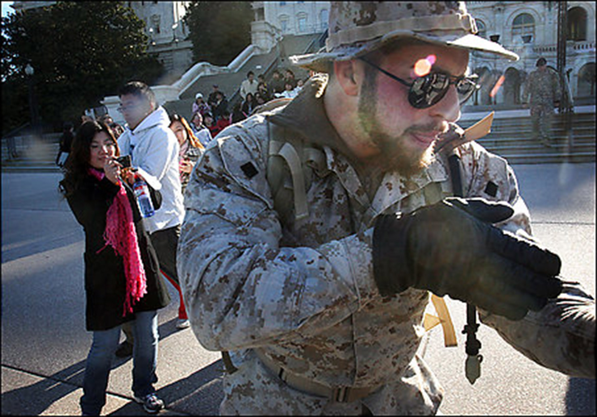 "st/streetthe Andrea Bruce/TWP  3/19/07 189148 Chinese tourists take photos of Adam Kokesh while he uses a pretend gun to ""detain"" volunteers protesting the war with him. Iraq Veterans Against the War ""patrolled"" around the Capitol and Union Station Monday as street theater. They ""detained"" volunteers during the peaceful protest against the war.   StaffPhoto imported to Merlin on  Mon Mar 19 16:56:01 2007"