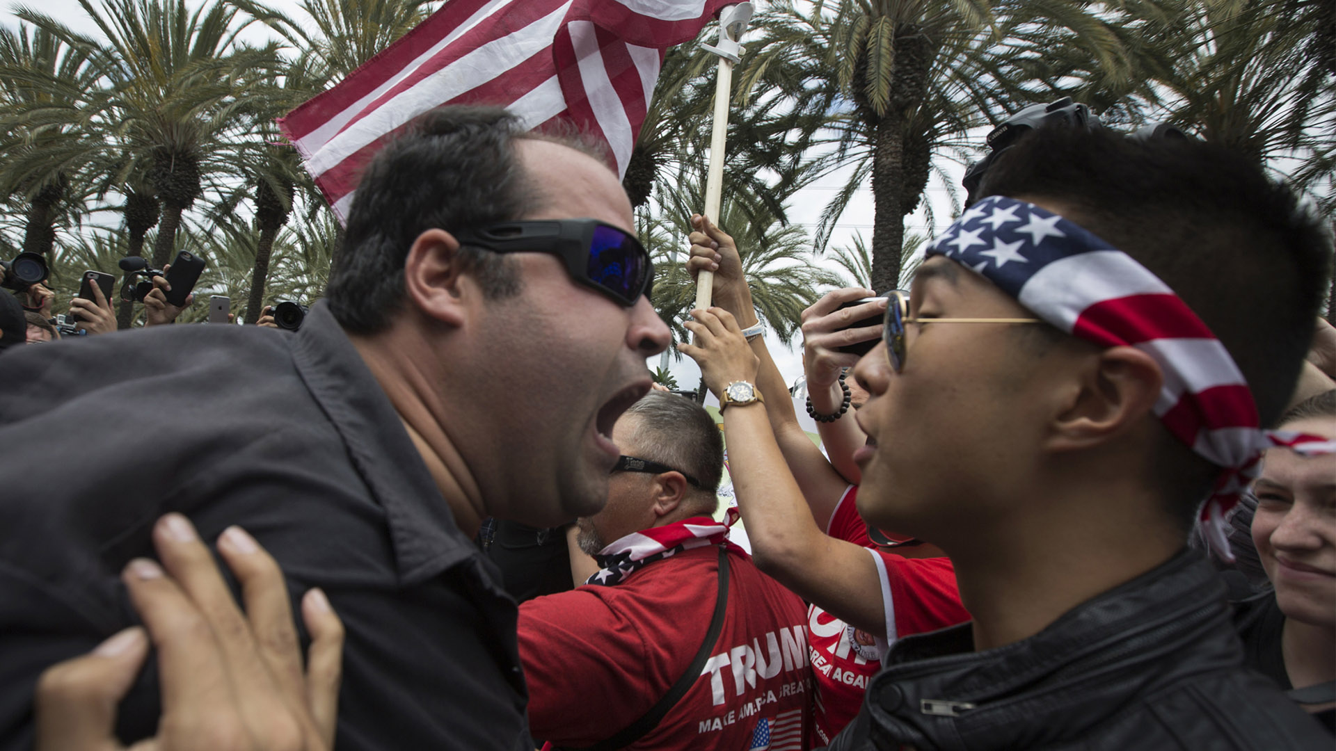 ANAHEIM, CA - MAY 25: An anti-Trump protester (L) and a Trump support clash outside a campaign rally by presumptive GOP presidential candidate Donald Trump at the Anaheim Convention Center on May 25, 2016 in Anaheim, California. Previous visits by the candidate to Orange County have sparked in protests that resulted in some arrests. The presidential candidates are campaigning in Southern California for the June 7 California primary. (Photo by David McNew/Getty Images)