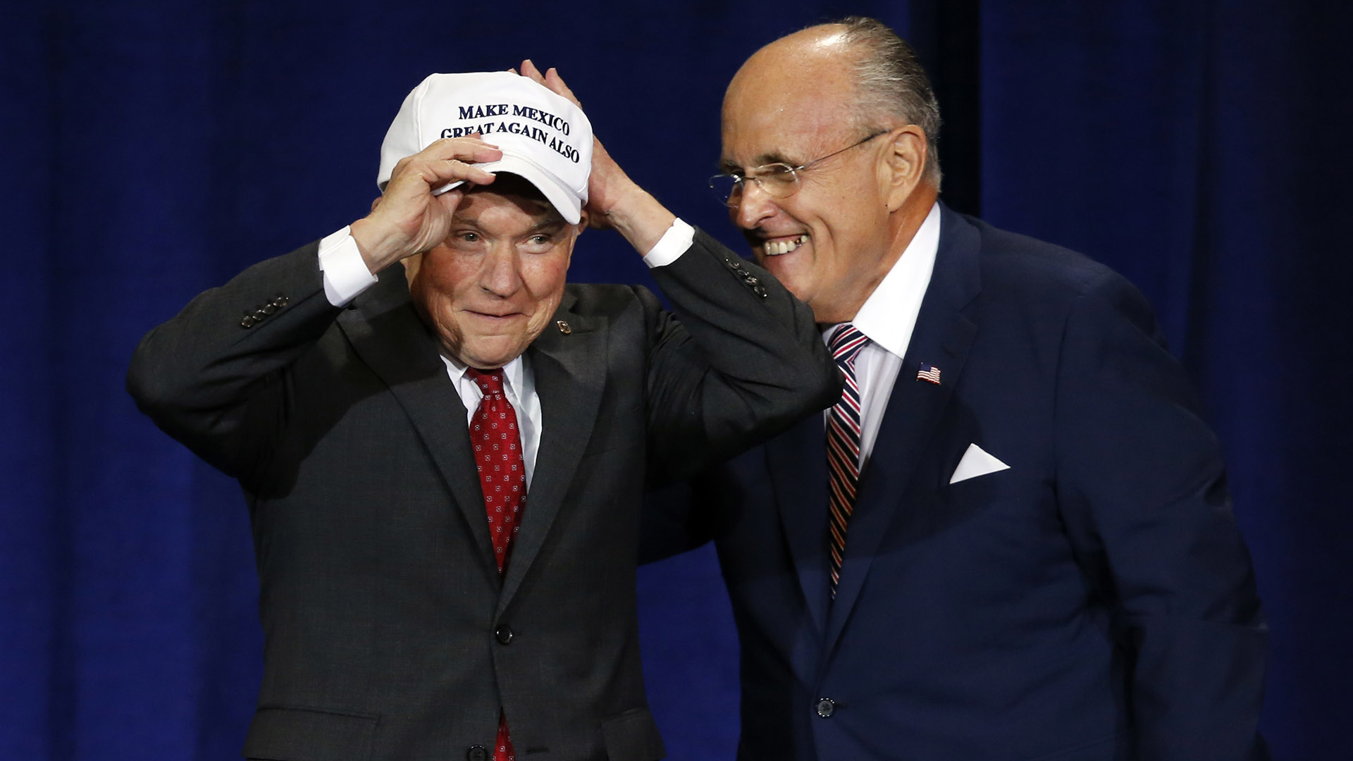 "Former mayor of New York CIty Rudy Giuliani, right, give U.S. Sen. Jeff Sessions, R-AL., a ""Make Mexico Great Again Also"" hat prior to Republican presidential candidate Donald Trump's speech during a campaign rally at the Phoenix Convention Center, Wednesday, Aug. 31, 2016, in Phoenix. (AP Photo/Ross D. Franklin)"