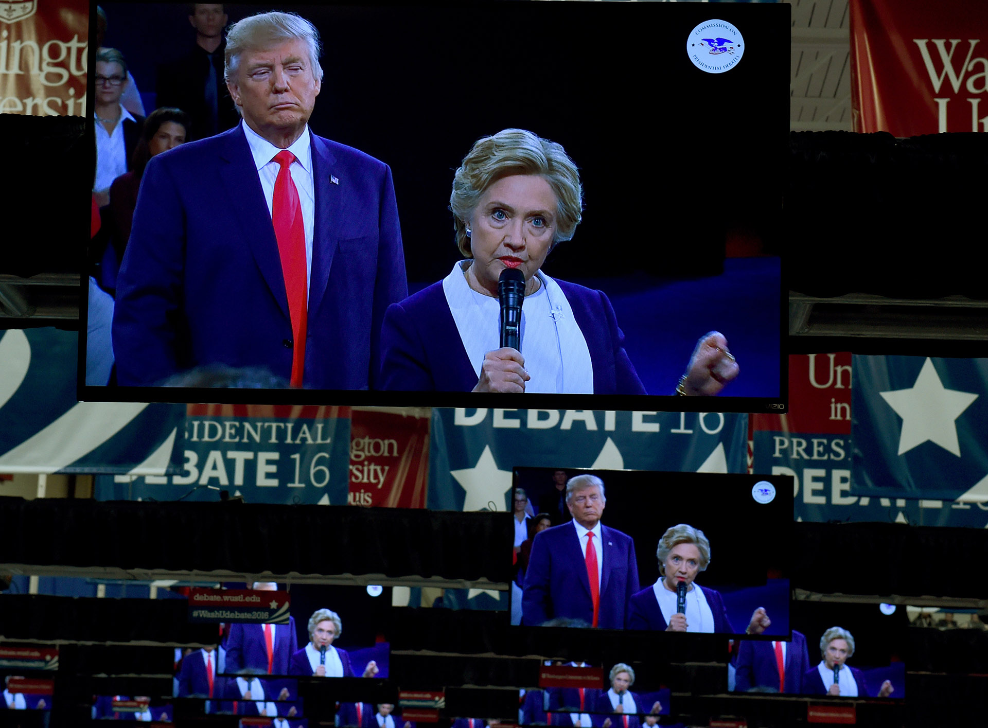 TV monitors in the press room show Republican nominee Donald Trump and Democrat nominee Hillary Clinton on stage as they participate in the 2nd debate at Washington University in St. Louis, Missouri October 9, 2016. / AFP / TIMOTHY A. CLARY (Photo credit should read TIMOTHY A. CLARY/AFP/Getty Images)